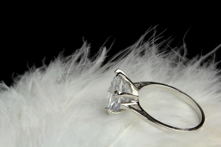 Diamond solitaire ring on white feather with black background