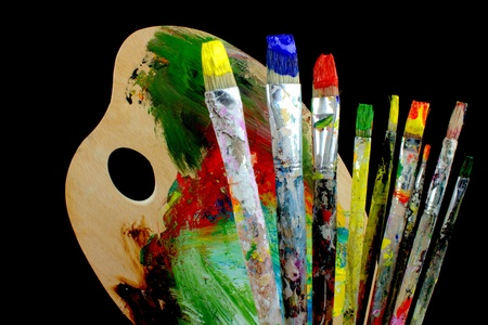 Paintbrushes and palette on black background