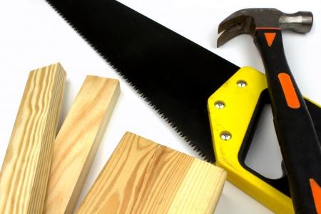 serrucho: Las tablas, serrucho y un martillo sobre un fondo blanco