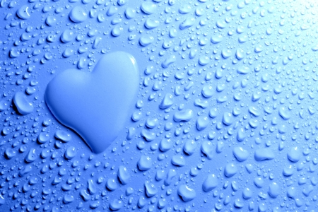 Water drops and heart shape on blue background photo