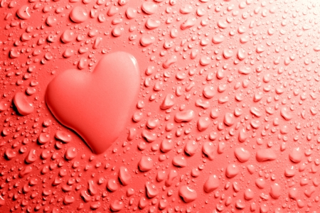 Water drops and heart shape on red background photo