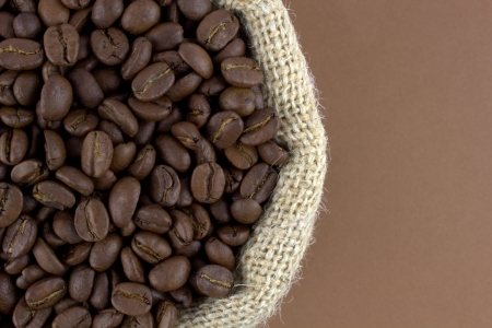 coffe beans: Coffee beans in a linen sack on brown background Stock Photo