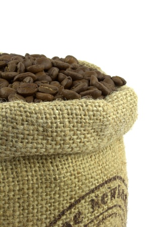 Roasted coffee beans and linen sack on white background