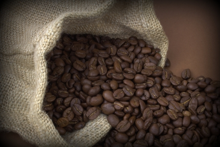 Coffee beans in a natural linen bag on brown background photo