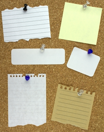 Various note papers on cork board Imagens