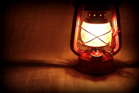 Oil lamp on burlap in dark