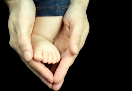 Baby foot in mother hands on black background  photo