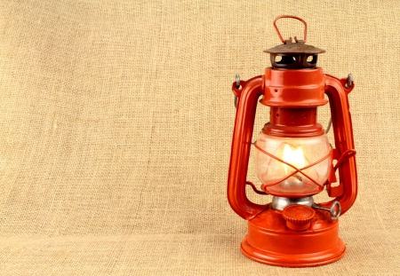 red oil lamp: Red oil lamp on burlap and copy space Stock Photo