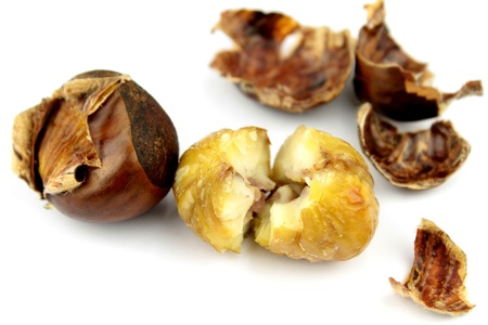 buckeye seed: Roasted chestnuts with shells on white background Stock Photo