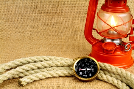 Old compass, oil lamp and rope on burlap photo