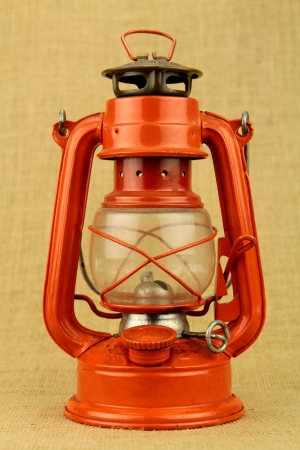 oil  lamp: Red oil lamp on burlap Stock Photo