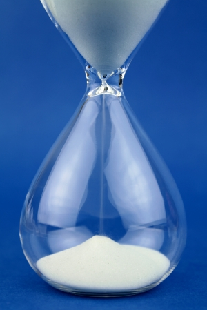 sand timer: Close up hourglass on blue background.