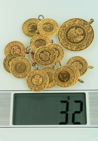 Gold coins on a jewelery scale photo