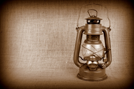 flame like: Old oil lamp on burlap and copy space Stock Photo