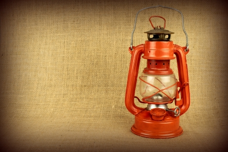 Red oil lamp on burlap and copy space photo