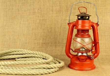 flame like: Red oil lamp and rope on burlap Stock Photo