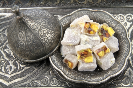 Turkish delight with pistachio nuts in traditional carved patterned metal plate  Archivio Fotografico