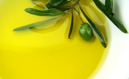 Olive oil and green olive branch in bowl