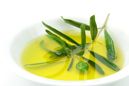 leaf close up: Organic olive oil and green olive branch in bowl   Stock Photo