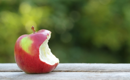 Bitten apple on wooden table in garden