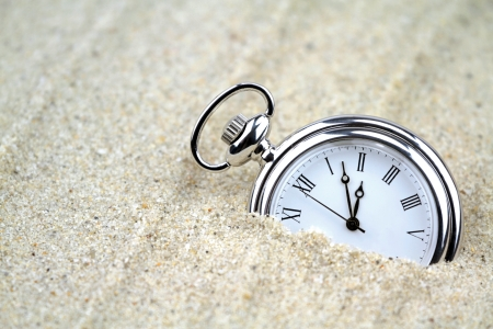 Pocket watch semi buried in the sand  photo