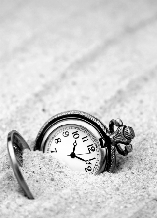 Antique pocket watch buried in sand  B W image  photo