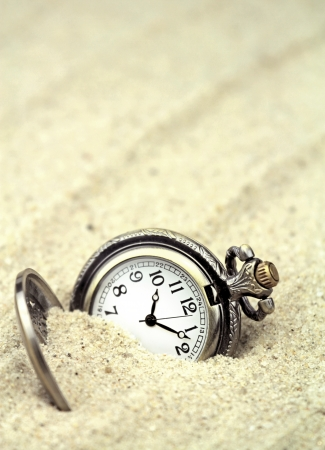 discarded metal: Antique pocket watch buried in sand