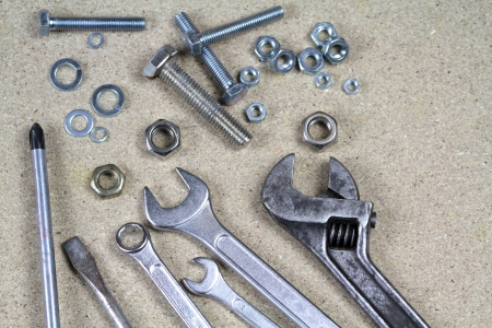 Wrench, monkey wrench and various bolts and nuts on particle board  photo