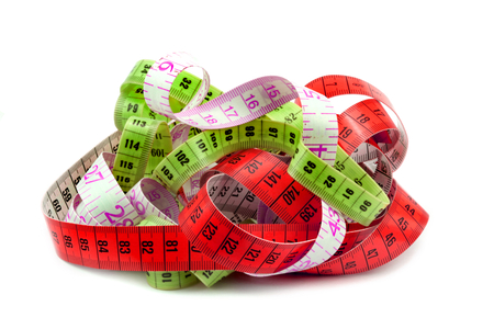 Various entangled measuring tape on white background photo