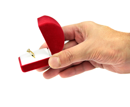 Hand holding a red gift box with wedding ring