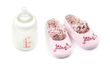 bootee: Baby bootee and bottle, on white background Stock Photo