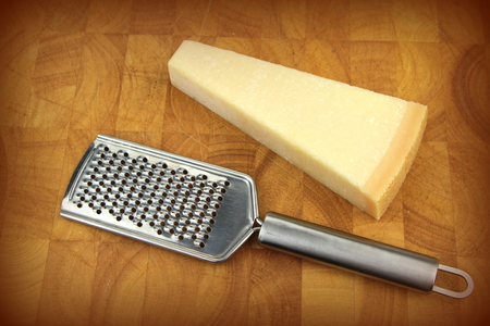 Parmesan cheese and grater on kitchen board  photo