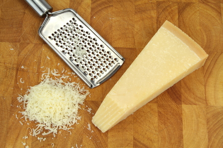 parmesan cheese: Parmesan cheese and grater on kitchen board  Stock Photo