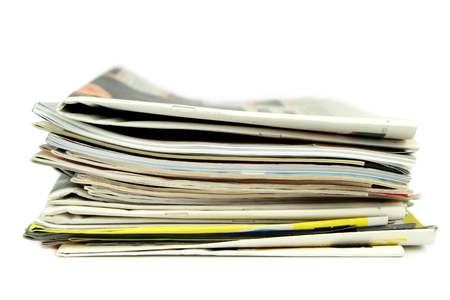 Pile of newspapers and magazines isolated on white background photo