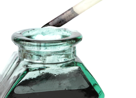 Quill pen and glass ink bottle ,on white background photo