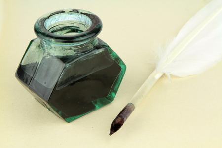 Quill pen and glass ink bottle on paper photo