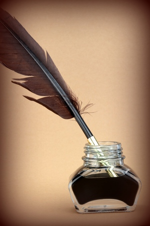 Quill pen in ink bottle on brown background  photo