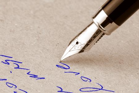 pluma de escribir antigua: Pluma fuente escrito en el papel, cerca de imagen Foto de archivo