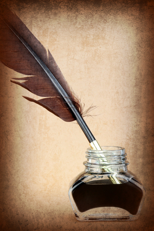 Quill pen in ink bottle on brown background  Vintage style image   photo