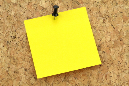 Yellow note paper on cork board  Macro image  photo
