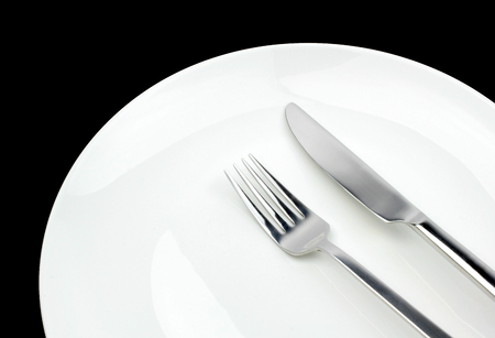 cooking ware: Fork, knife and plate on a black background.