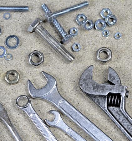 tuercas y tornillos: Llave, llave inglesa y varios tornillos y tuercas en los tableros de partículas.