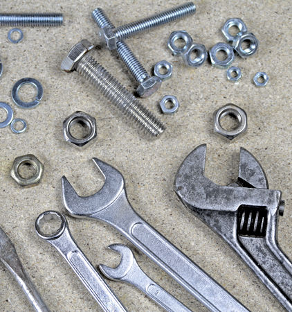 monkey nuts: Wrench, monkey wrench and various bolts and nuts on particle board.