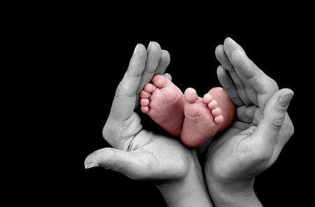 pie bebe: Pie del bebé en manos de la madre sobre fondo negro Foto de archivo
