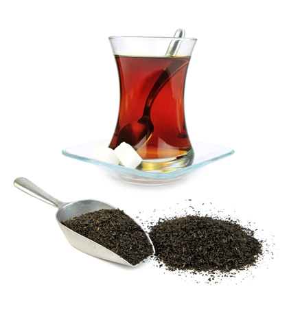 Turkish tea in traditional glass and dry black tea leaves