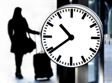 lateness: Station clock and a passenger waiting with baggage Stock Photo