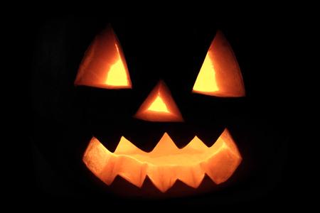 Halloween Kürbis mit gruseligem Gesicht in Dunkelheit Standard-Bild