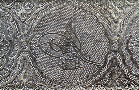 cipher: Ottoman tugra sign carved and patterned on a silver metal surface
