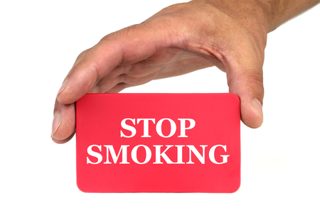 card stop: Hand holding and showing a red card with  STOP SMOKING  text