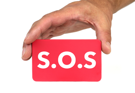 forewarn: Hand holding and showing a red card with  S.O.S  tex Stock Photo